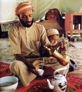 Beduinen zerkleinern die gerösteten Bohnen im metallenen Mörser und machen dabei rhymische Musik als Einladung zum Kaffeetrinken.